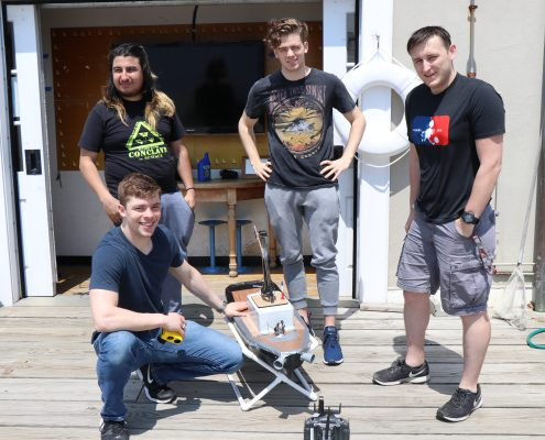 Four male students stand on the dock at the MIT Sailing Pavilion with a surface vehicle resembling a miniature boat that they developed