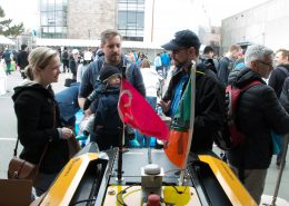 MIT AUV Lab's Paul Robinette talks to a couple with a baby about a yellow AUV on display