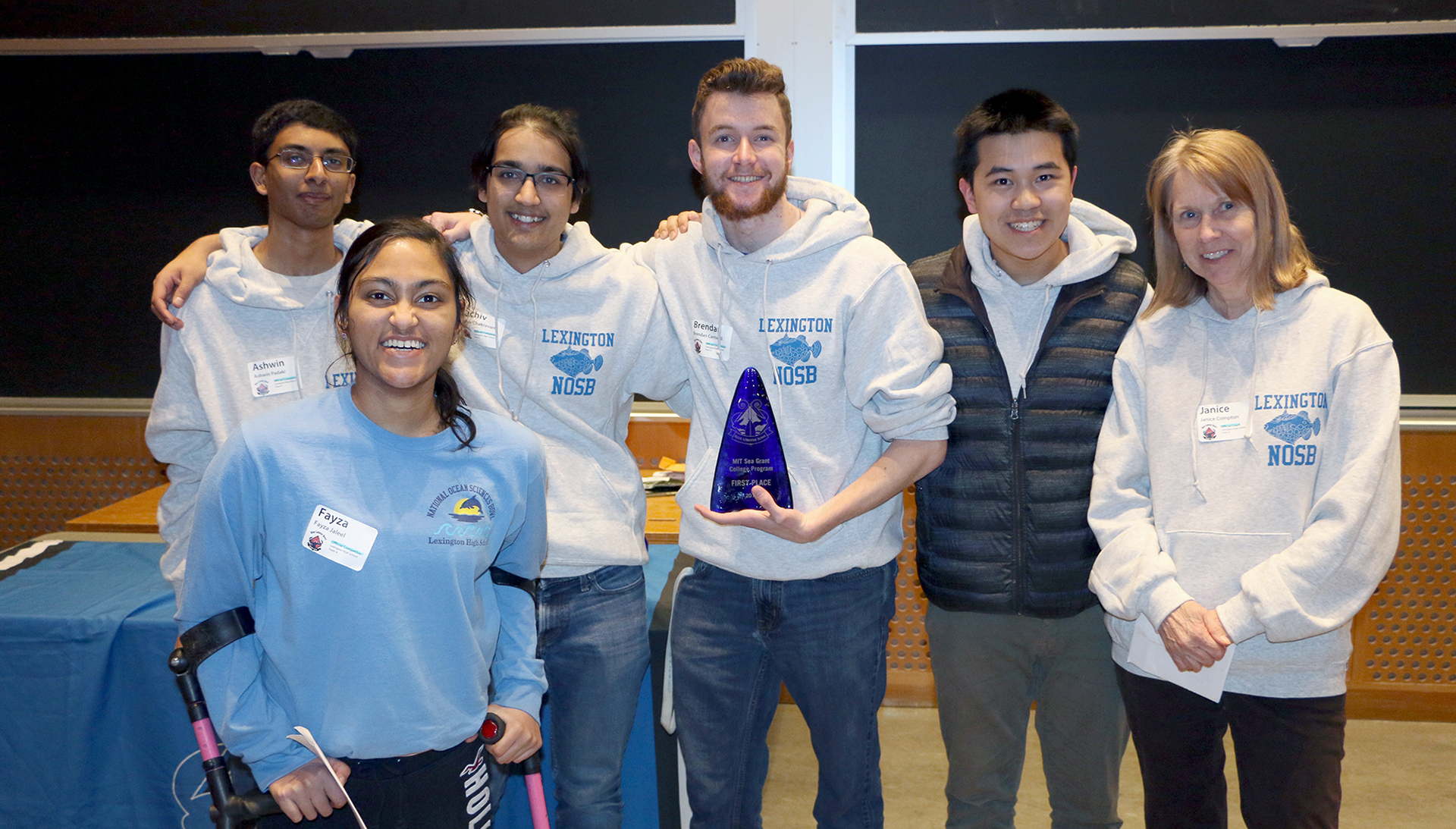Five students and a teacher posing with a blue glass award for a photo as the first place Blue Lobster Bowl team