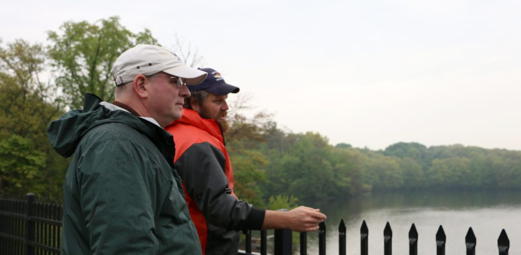 Two representatives from MIT Sea Grant and the MA DMF wearing baseball caps and rain gear look out over the Mystic Lakes