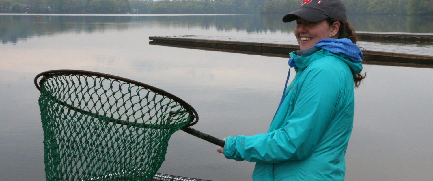 A student wearing a baseball cap and rain gear holds a large green net over a fish holding pen in the lake