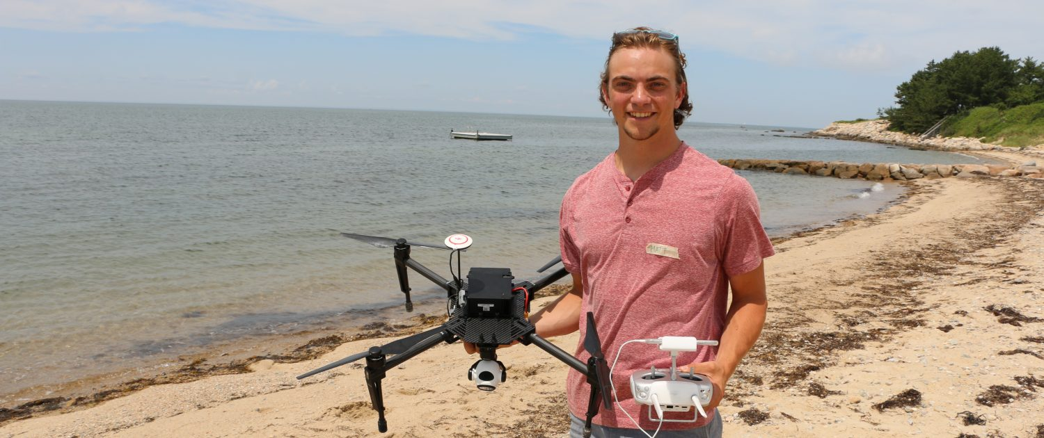 A male student holds a drone and controller while standing on a sandy shore on a beach
