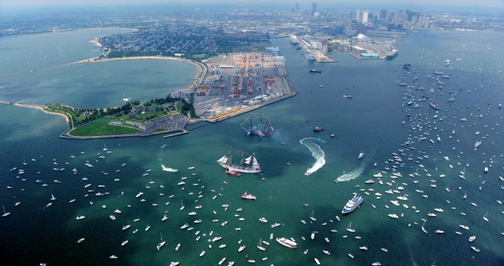 An aerial shot of a blue-green Massachusetts Bay and Castle Island with many boats and a couple of tall ships