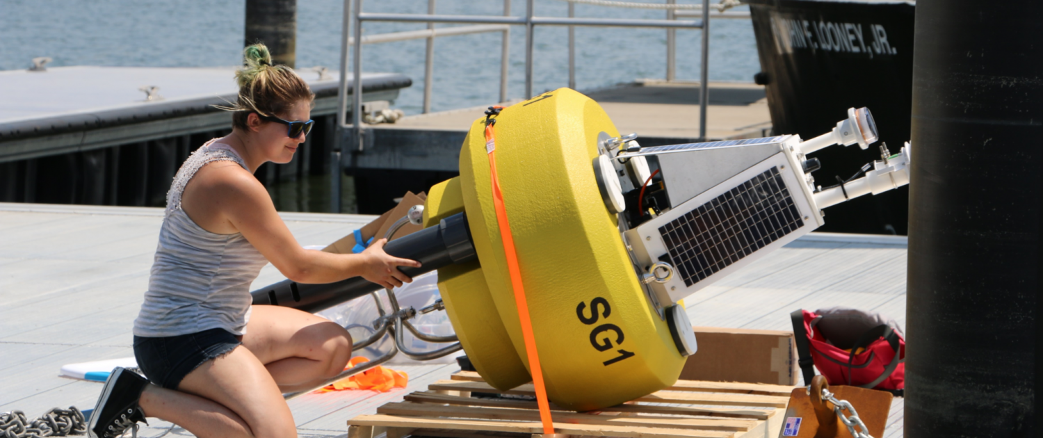 A female student kneels next to a yellow data buoy to add a final part on a dock by the water