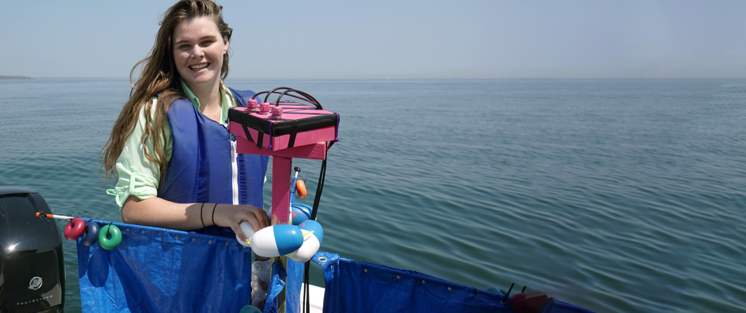 MIT student on a boat holding the ocean drifter she developed with the AUV Lab