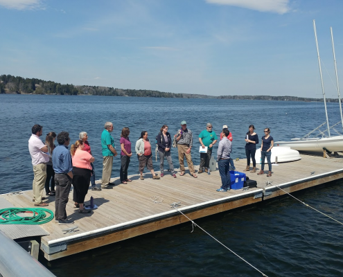 A group of scientists and volunteeres gathered on a dock for Shell Day last year