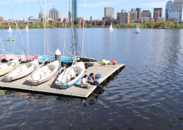 Sailboats on a dock at the MIT Sailing Pavilion with the Boston skyline in the background with the Charles River