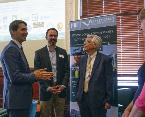Rep. Dylan Fernandes, Matthew Charette and Michael Triantafyllou talk after a presentation on the Blue Economy at the State House