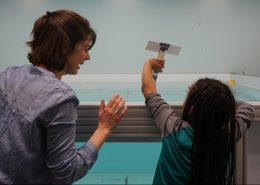 A woman and a child from behind about to drop a cardboard model into a large tank of water.