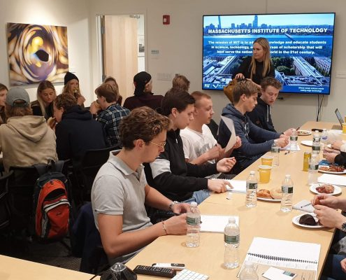 A group of students sitting for a presentation with a female speaker in front of a screen displaying a picture of the MIT campus