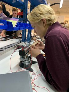 A student working with wires and tools in the MIT Sea Grant Teaching Lab