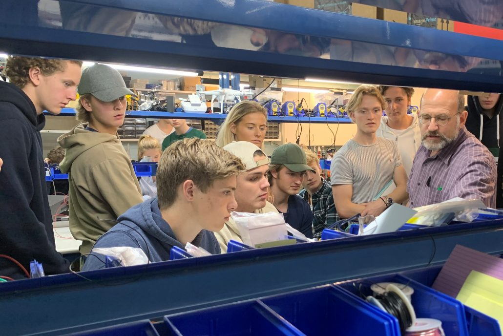 A group of students in a makerspace workshop listening to an instructor