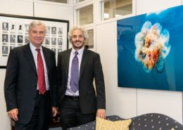 Senator Whitehouse meets and Keith Ellenbogen stand next to a large image of a jellyfish floating in blue water.