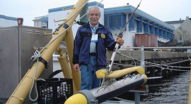 Marty Klein on a dock with a submersible piece of underwater engineering equipment