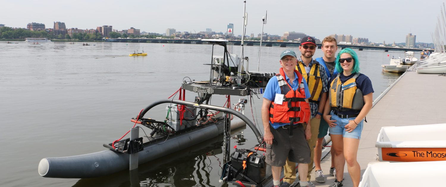 MIT AUV Lab team stands by REX, one of their autonomous vehicles, at the boat dock