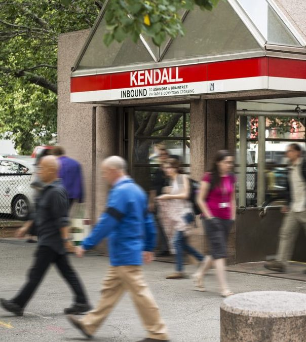 Kendall Square MBTA train station entrance with a red sign and people walking by