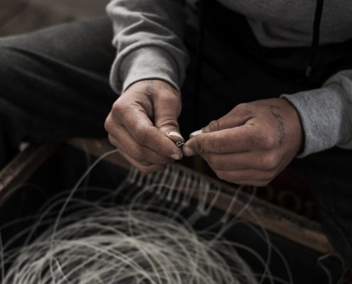 Two hands tying knots in fishing line